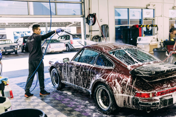 A detailer washing a Porsche in a wash bay with Free-Flow.