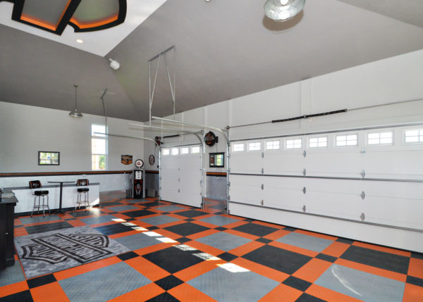Garage with alloy, black, and orange Harley-Davidson garage flooring tiles.