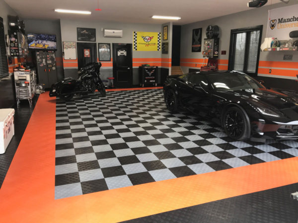 A Harley and a Corvette in a garage with Harley-Davidson garage flooring